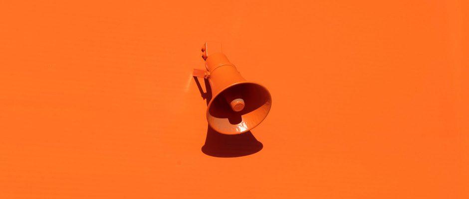 Foto mit Megaphon auf orangenem Hintergrund zu Pressemitteilungen HateAid