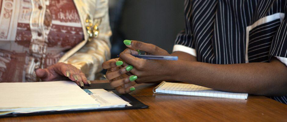 Hände mit grünem Nagellack und Stift
