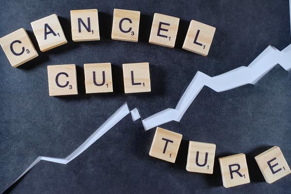 Scrabble-Steine, die das Wort Cancel Culture auf schwarzer Pappe legen.