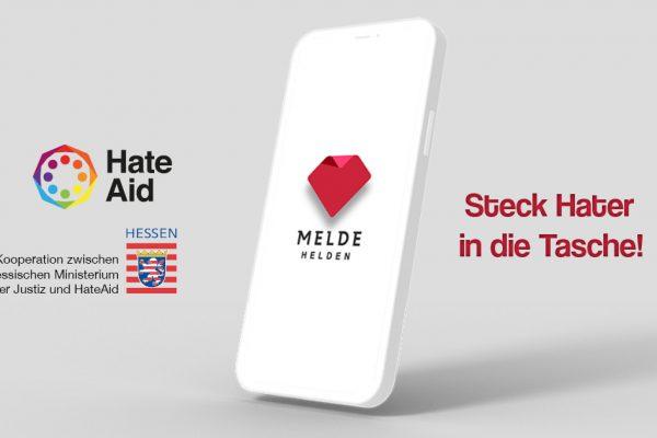 Handy mit MeldeHelden Logo, den Logos von HateAid und dem Hessischen Ministerium der Justiz sowie dem Slogan Steck Hater in die Tasche